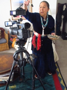 Mary J. AshkiiLgaii Wheeler, Navajo elder, smudges (clears the energy field) of the new cameras with sage before the first shoot. A traditional Native American practice.